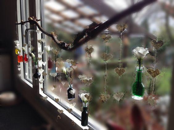 Fenster-Dekoration:  1. Einen Ast an Fenster oder Wand hängen 2. Herzen aus einem schönem Papier/alten Buch stanzen und an einen dünnen Faden binden 3. Kleine Glasfläschchen mit buntem Wasser füllen und anschließend eine weiße Blume hineinstecken. | Die Blumen nehmen die jeweilige Farbe an und schon hat man eine wunderschöne, bunte Deko! Viel Spaß :) |