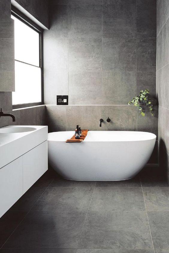 Antraciet Scandinavische badkamer inrichting inspiratie met vrijstaand wit bad. Daarnaast een egaal wit zwevend badmeubel met zwarte inbouwkraan. Antraciet 60x60 tegels zijn super hier! Op zoek naar een Scandinavische badkamer? Klik dan op de foto!