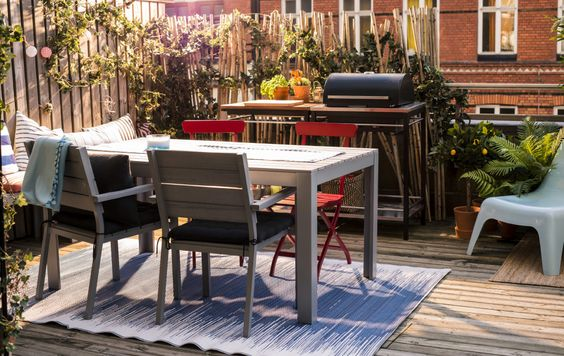 A shot of a balcony with a table and chairs, bench, grill and lots of plants..