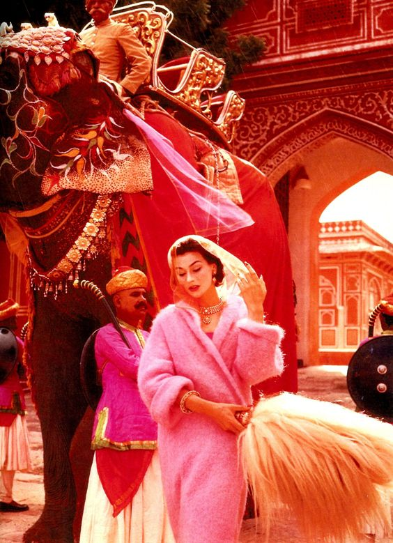 Anne Gunning in a pink mohair coat outside the City Palace, Jaipur, India, Vogue, November 1956