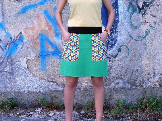 Falda verde (tela algodón y lino), bolsillos de flores multicolor. Cintura elástica negra.