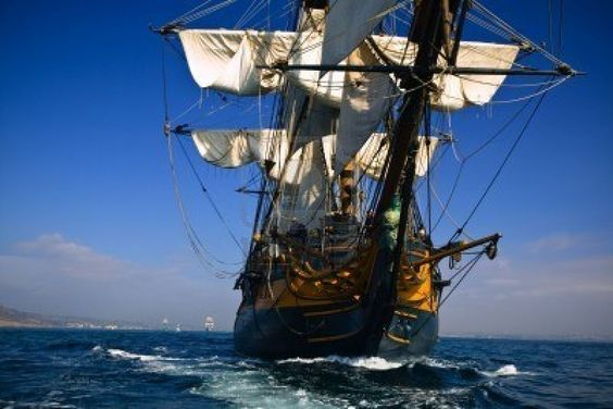 HMS Surprise Sailing Ship at Sea under full sail with tall ships in the background. Stock Photo