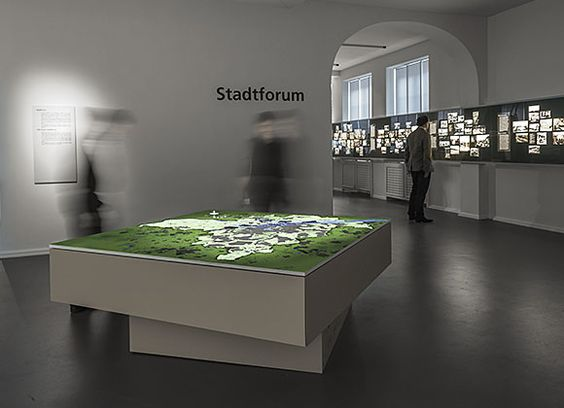 The table top is a square 3.5 m² area showing a landscape map of the Hamburg area. Visitors use a mechanical time wheel to navigate their way through eleven epochs and discover how the structure of the city and the landscape were transformed over time.