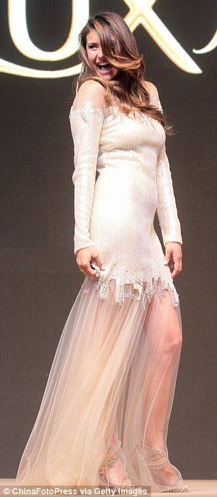 White hot: The star wore a long sleeved heavily embellished dress which ended mid-thigh be...