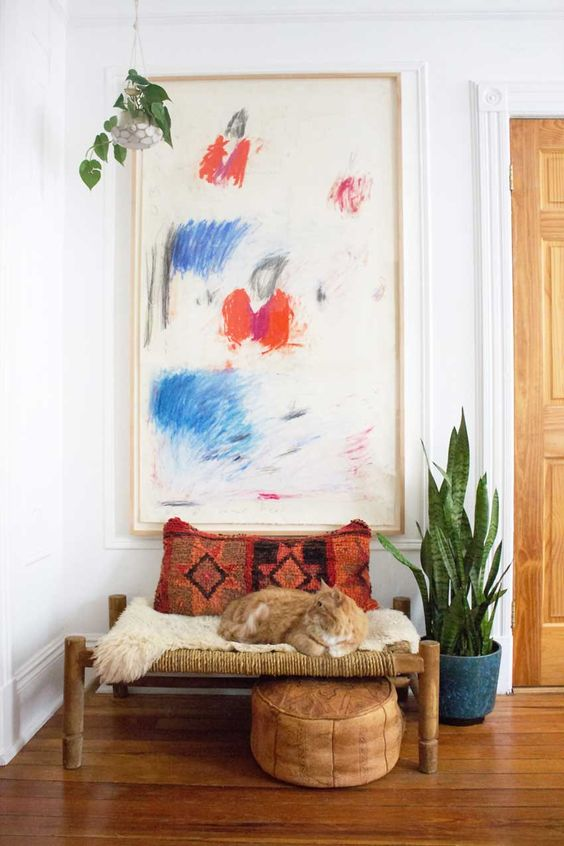 Boho chic vignette with abstract art and cat on a bench in a Brooklyn apartment.