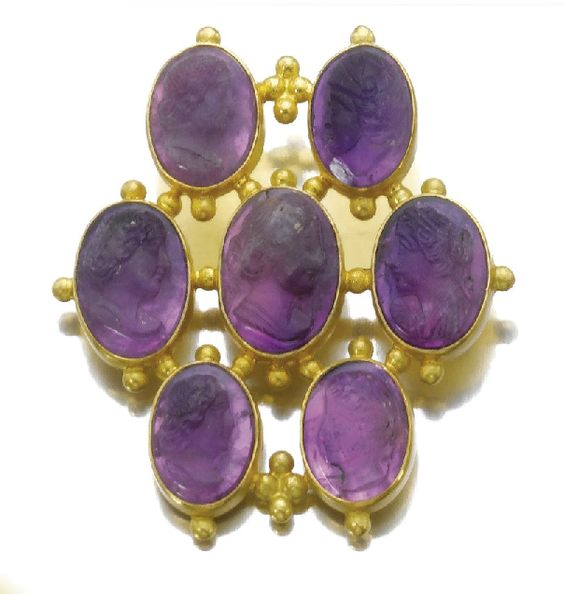 [Close up of the brooch to show profiles] Gold and Amethyst parure, circa 1869. Comprising a necklace, a bracelet, a brooch and a pair of earrings all set with carved amethyst depicting right and left profiles, accented with gold granulation.