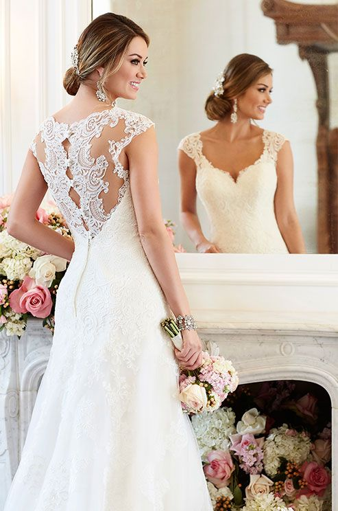 This romantic A-line wedding dress from Stella York boasts eye-catching lace cap sleeves and a scalloped-lace illusion back with pretty fabric-covered buttons. Stella York, Spring 2016: