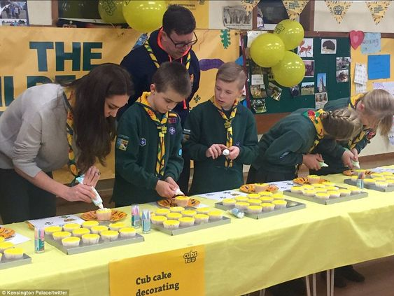 A beaming Duchess helps young Cub Scouts decorate cupcakes laid out as part of a spread to help mark the organisation's 100th anniversary on Wednesday night, at an event just a few miles from Kate's Anmer Hall home: