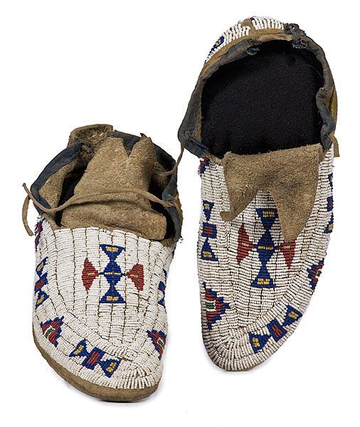 Arapaho beaded hide buffalo hide moccasins -  Thread and sinew-sewn using bead colors of white, greasy yellow, dark blue, and red white-heart; cuffs edged with blue cotton; hint of yellow pigment on hide, length 10.5 in. late 19th century