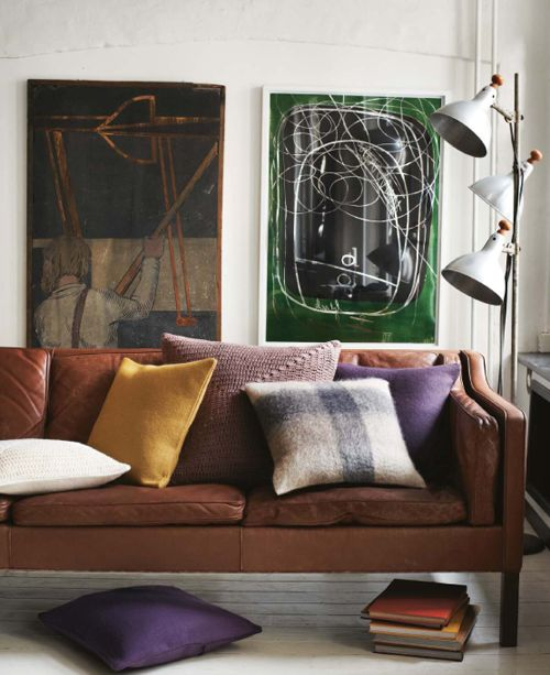 leather sofa + purple and yellow pillows