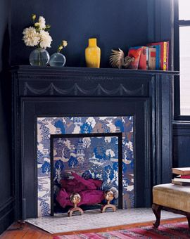 """from Domino Magazine: unused fireplace + wallpaper in a busy pattern + magenta-painted """"logs"""", photo by ANNIE SCHLECHTER"""