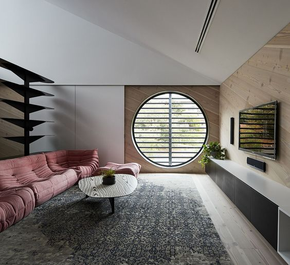 Round window and plush pink sofa add a different dynamic to the room