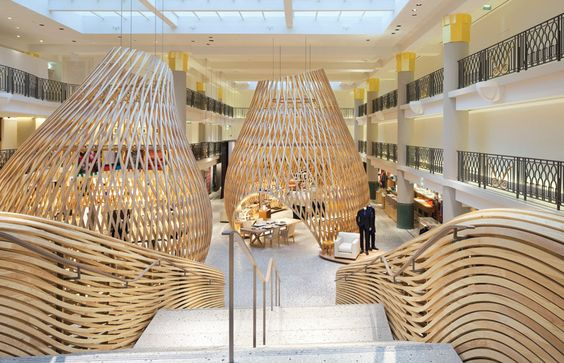 A former swimming pool in Paris is transformed into a sensuous interior for Hermès Rive Gauche, with sculptural timber pods designed by RDAI.