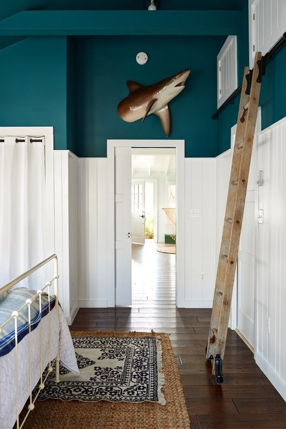 funky cabin interior, ladder to loft, iron bed, shark on wall, white wood walls, turquoise.