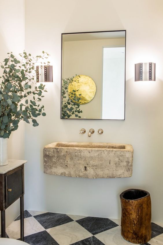 In a bathroom in Leigh Herzig's Spanish villa, antique black-and-white marble tiles in the powder room and a limestone trough sink from Big Daddy's. The Custom Metal Mirror is from Restoration Hardware and the sconces are 1950s Dutch from LA vintage lighting shop ReWire.