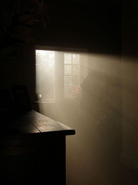 dusty sunlight through an open window into a dark room