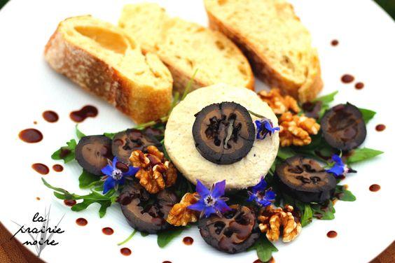 Hausgemachter Cashewfrischkäse mit eingelegten schwarzen Nüssen, Walnüssen, Rucolasalat und Baguette.