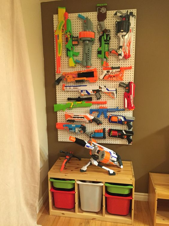 Nerf gun storage! Large guns on the pegboard; small guns, ammo, accessories, targets, and safety glasses in the unit below. Perfect!