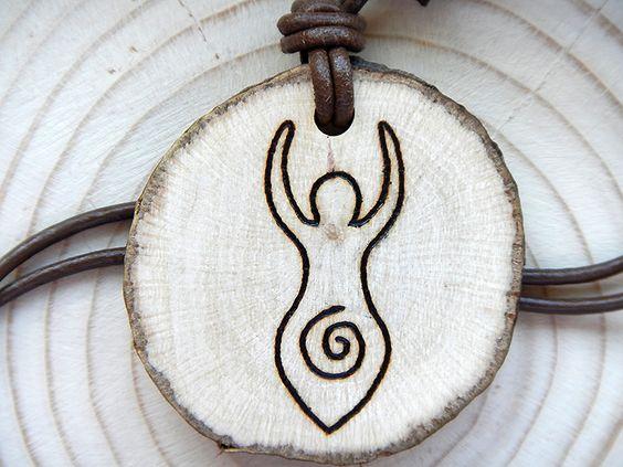 Amulett aus heimischem Astholz aus der Region mit einem durch Brandmalerei verziertem Spiralgöttin-Motiv.