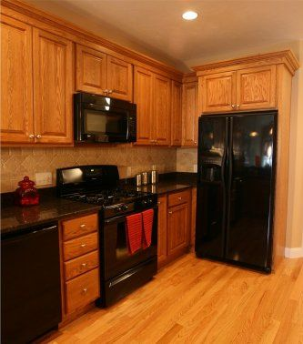 Kitchen with oak cabinets with black appliances bing for Black and brown kitchen cabinets