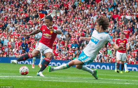 Newcastle United defender Fabricio Coloccini slides in to block a shot from Manchester United forward Memphis Depay