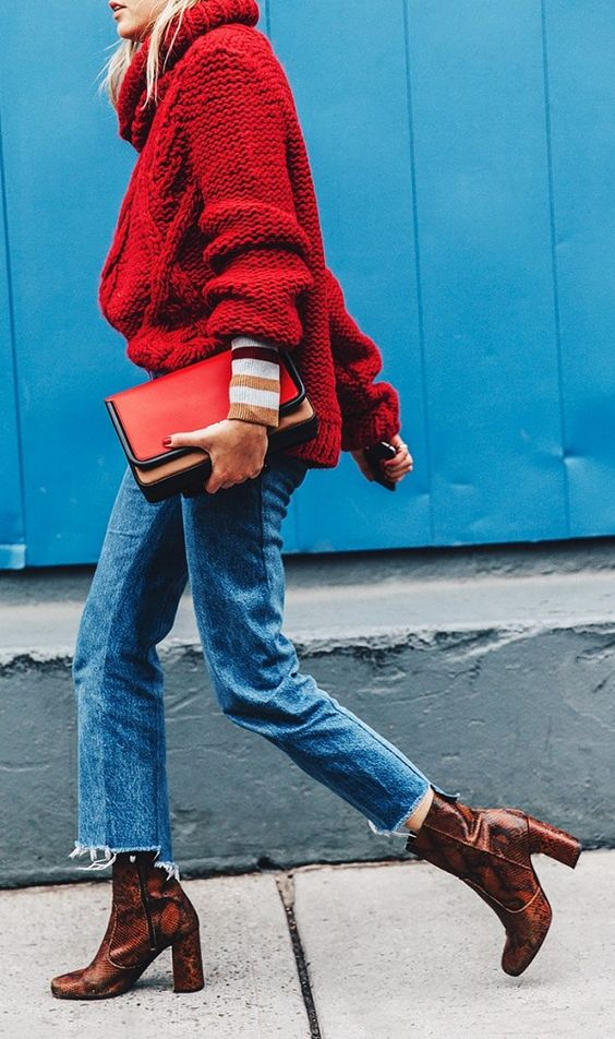 Camille Charriere wears an oversize red sweater with a red clutch, Vetements jeans, and reptile-print boots:
