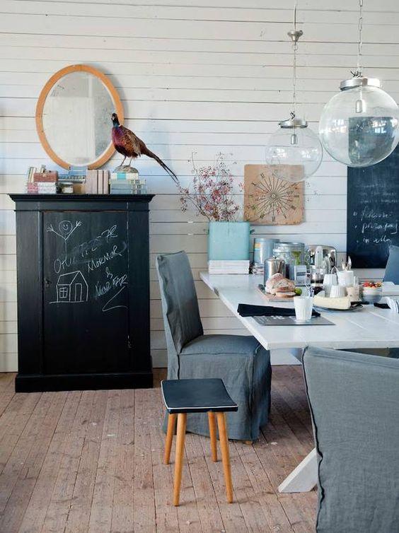 Białe malowane deski na ścianie tworzą neutralną bazę dla ciekawych dodatków i mebli w jadalni. W oczy rzuca się szafka pomalowana czarna farbą tablicową oraz krzesła w ciemnoszarych, lnianych pokrowcach. Kompozycję uzupełniają nowoczesne szklane lampy w formie kuli oraz przekornie ustawiony na szafce wypchany bażant.