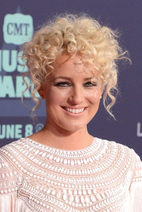 To get singer-songwriter Cam's modernized curly updo, Delgado recommends pinning up the back curls, creating a short-haired look that can be incorporated with twists or braids for more polish. Leaving the bangs and face-framing tendrils out also softens the style, showing off the natural texture of your curls.