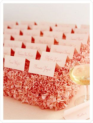 Escort cards on a bed of pink carnations