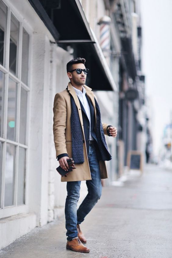 Shop this look on Lookastic: https://lookastic.com/men/looks/overcoat-blazer-dress-shirt-skinny-jeans-brogues-scarf-gloves-sunglasses/13367 — Black Sunglasses — White Dress Shirt — Navy Blazer — Navy Polka Dot Scarf — Camel Overcoat — Dark Brown Leather Gloves — Blue Skinny Jeans — Brown Leather Brogues
