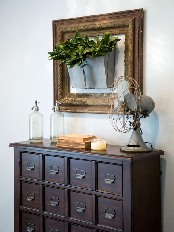 From Fixer Upper - hang an old galvanized metal scoop inside of an empty picture frame and fill it with faux greenery
