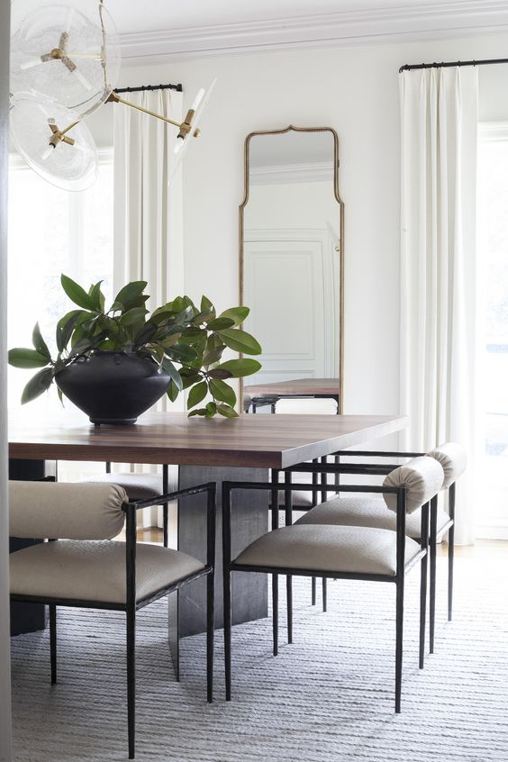 Tall arched mirror in the dining room + white walls + white curtains + modern glass bulb chandelier + rectangular wood dining table + large vase with greenery centerpiece + modern dining chairs | Lucy and Company