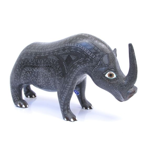 """This black rhinoceros was carved with great attention to detail and painted with very white lines. The Zapotec theme of the design is representative of the ancient culture the people of San Martin Tilcajete in Oaxaca still practice and depict in their artworks. Made by the talented Hernandez family"":"