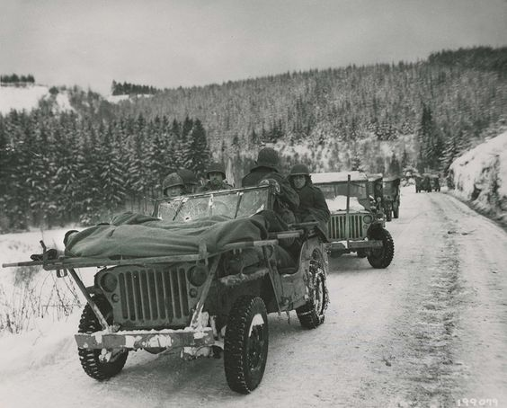 Bullet holes in the windshield of this Jeep are a                   testament to the faithful service of the Medics of the                   84th Division as they evacuate wounded soldiers in                   their makeshift Jeep ambulance. The Medics are                   carrying two soldiers wrapped up in blankets to keep                   them warm in the frigid cold. The litters are strapped                   to a makeshift frame attached to the flat-hooded Jeep                   4x4. This Jeep caravan was part of the 1st Battalion,                   334th Infantry Regiment. Image was taken on January                   9th, 1945. Thanks to...