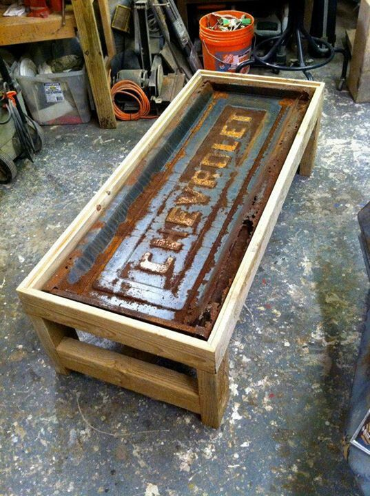 Coffee table out of old tailgate. Has a lot of potential. Glass top display. LED light strips. Could sub plumbing pipe base and reclaimed wood.