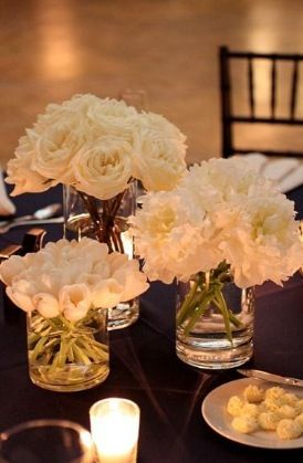 Simple and elegant. White wholesale flowers in clear glass vases make for stunning and versatile arrangements of wedding flowers! Notice also the use of multiple types of flowers, not arranged together, but in their own vases of different sizes. This picture is proof that DIY wedding flowers can be simple, elegant and easy to arrange!