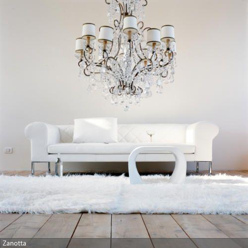 Der prunkvolle Kronleuchter passt optimal zum neobarocken Design. Durch die Einrichtung in reinem Weiß entsteht ein luxeriöser Stil, der Shaggy-Teppich unterstreicht…