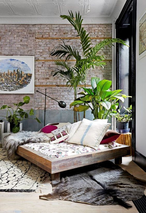 Brick wall exposed in living room with rich color palette and tall indoor plants: