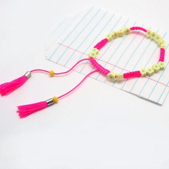 Armband Hanna Neon pink & gelb. NOI home & fashion | Colour up you life - mit diesen farbenfrohen Armbändchen.Gelbe Steinchen in Form eines Blümchen in Kombination mit dem kontrastfarbenen Bändchen machen es besonders. Es lässt sich in seiner Grösse verstellen und am Ende des Bändchens baumeln Mini-Troddeln.   Maße: Größe verstellbar  Material: Polyester mit Perlen #NOIhamburg #armband #troddeln #fashion #girlstyle #schmuck
