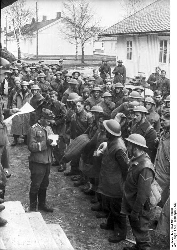 """April 1940 Drontheim Norwegen, deutscher Hauptfeldwebel """"Spieß"""" (hier im Dientgrad: Oberfeldwebel (OR-7)) vor britische Kriegsgefangene.  Scherl UBz.: Gefangene Engländer, die zunächst in Drontheim in Gefangenenlagern untergebracht wurden. Die Tommies hatten sich ihren """"Einzug"""" in diese norwegische Hafenstadt sicherlich anders vorgestellt. PK-Eitel Lange-Scherl 2.5.1940 [Herausgabedatum] [Drontheim.- kriegsgefangene britische Soldaten, Hauptfeldwebel mit Notizblock, deutsche Wachsoldaten]"""