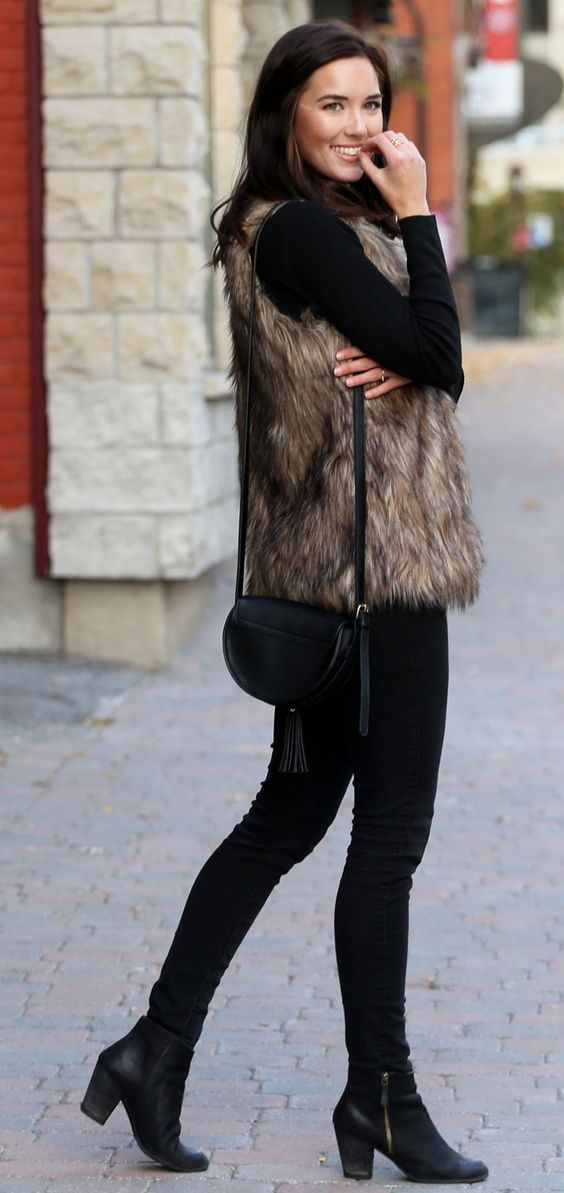 How to add some winter vibes to an all black outfit. Fashion blogger Marie's Bazaar wears a faux fur vest from Dynamite Clothing over a cutout black sweater and these must-have black booties.: