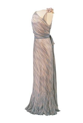 Queen Maud's personal dressers made notes about what garments she wore on specific occasions. These indicate that she wore an evening dress of 'blue and silver-grey striped chiffon' from Reville-Terry on Midsummer Eve 1935. Although no label survives, this gown matches the description very well. Simple in its style and cut, the dress relies entirely on the clever arrangement of the striped fabric for its visual impact.