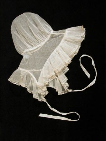Cap - White net, full crown pulled up by cord in seam, attached to band, pointed at sides, with frill all the way round trimmed with narrow lace. back gathered by cord. 1820 - 1830 (circa)