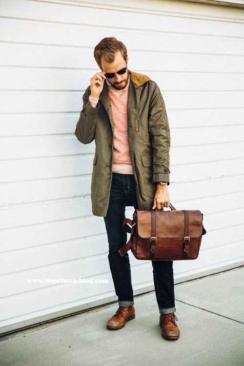 Rock an olive parka with navy jeans if you're going for a neat, stylish look. Dress it up with brown leather derby shoes. Shop this look for $502: http://lookastic.com/men/looks/crew-neck-sweater-parka-sunglasses-jeans-messenger-bag-derby-shoes/4754 — Pink Crew-neck Sweater — Olive Parka — Black Sunglasses — Navy Jeans — Brown Leather Messenger Bag — Brown Leather Derby Shoes