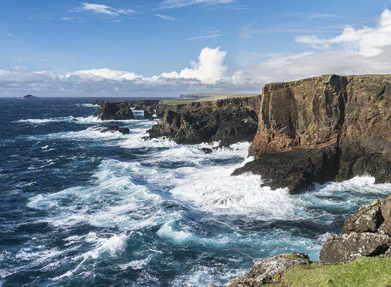 the ocean meets tall coastal cliffs