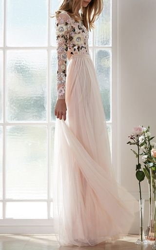 This long sleeve **Needle & Thread** dress features a floral sequin embroidered bodice with a jewel neck and open back, a fitted waistband, and a floor length column skirt rendered in tulle.