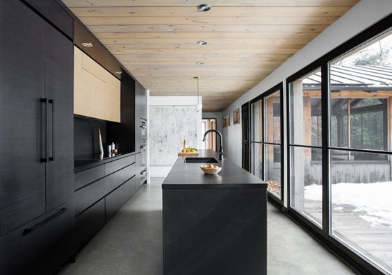 This Modern Black Kitchen Stands Out Against The Light Floors And White Walls And Fits Right In Modern Black Kitchen Black Kitchens Minimalist Kitchen Design