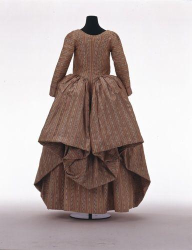 """Rear view, robe à la polonaise, Europe, c. 1785. Striped salmon silk pékin """"chiné à la branche""""."""