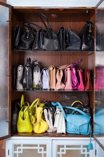 Color coded handbag storage on a boodshelf. this is a great way to repurpose an old china cabinet! #closet #handbags #storage
