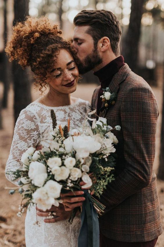 An all lace bridal gown + a warm suit jacket were the perfect fashion combo at this cabin wedding inspiration | Image by Jonnie + Garrett